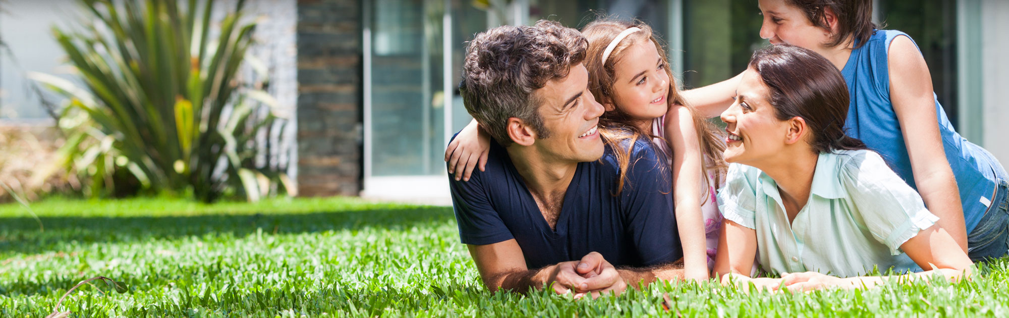 Man and daughter laying on grass